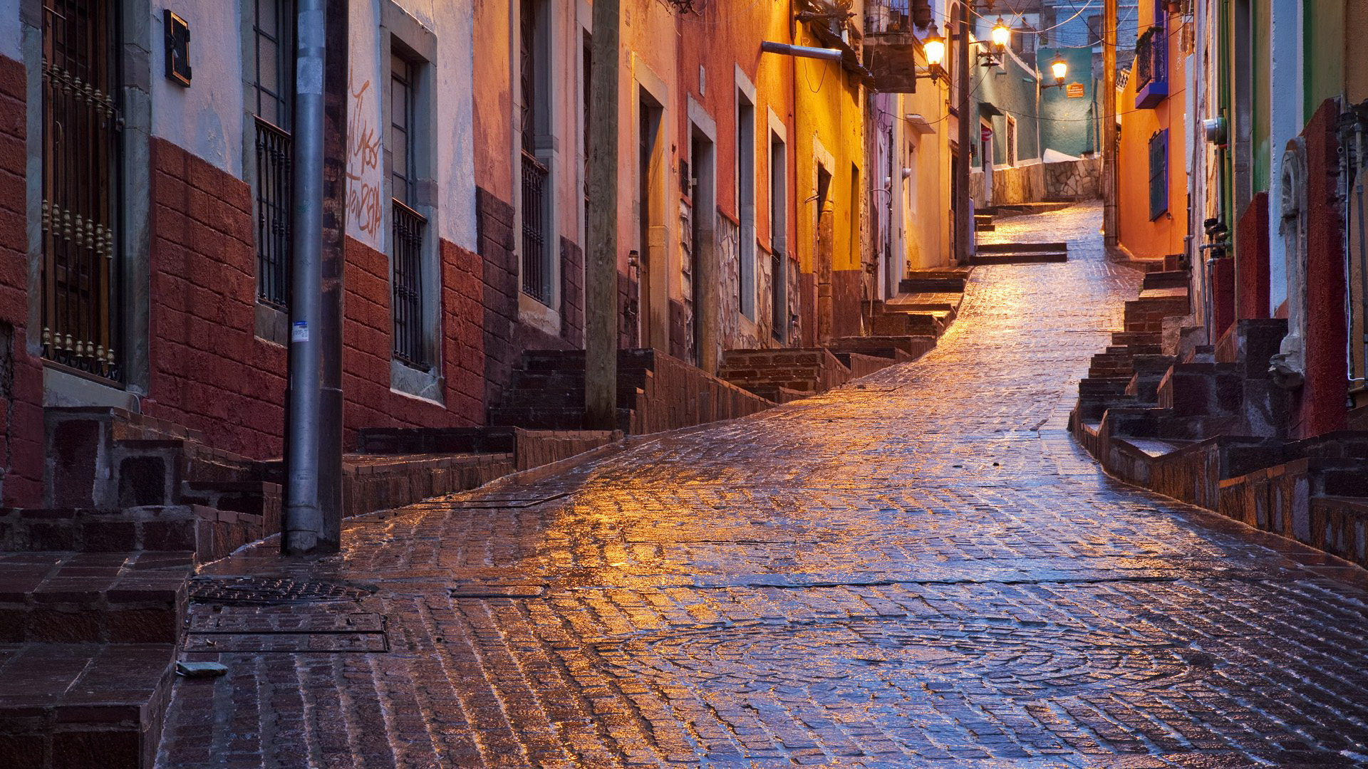 Taken before dawn in a light rain in Guanajuato, Mexico. The water slicked cobles brilliantly reflected the streetlights and sky.